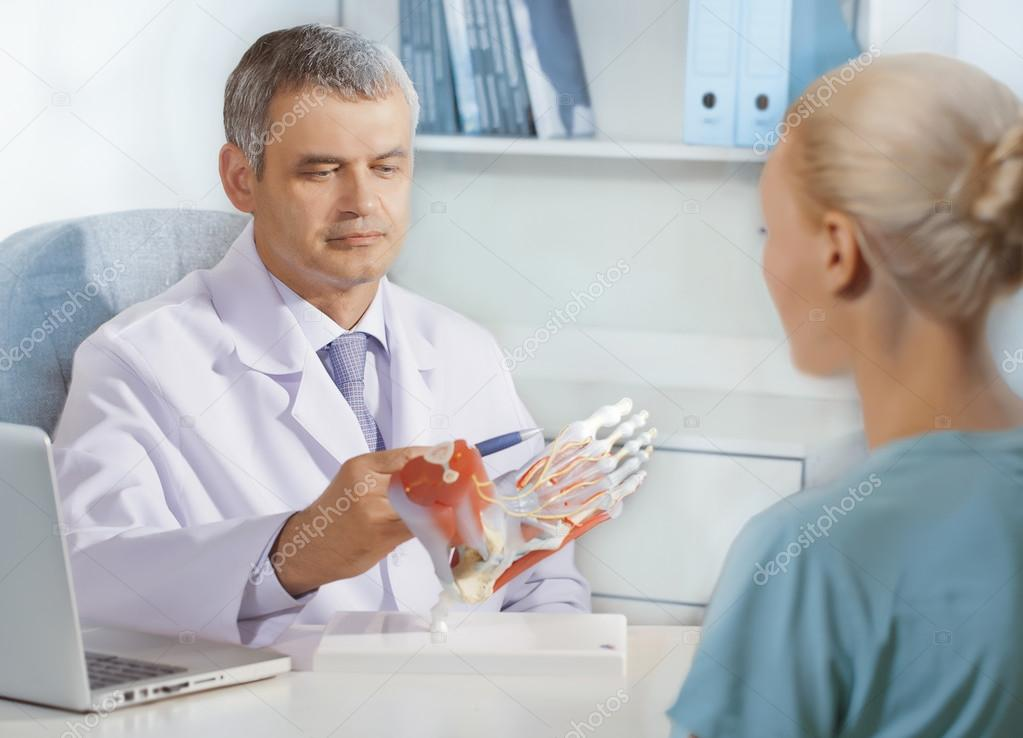 Orthopedic Doctor In His Office With The Model Of Feet Stock Photo