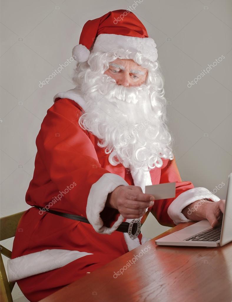 Papai Noel Usando Seu Cartão De Crédito Para Comprar On Line Stock