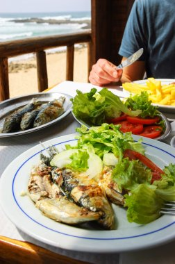 Traditional Portuguese lunch -  grilled sardines - at restaurant terrace with ocean beach view. Algarve, Portugal.