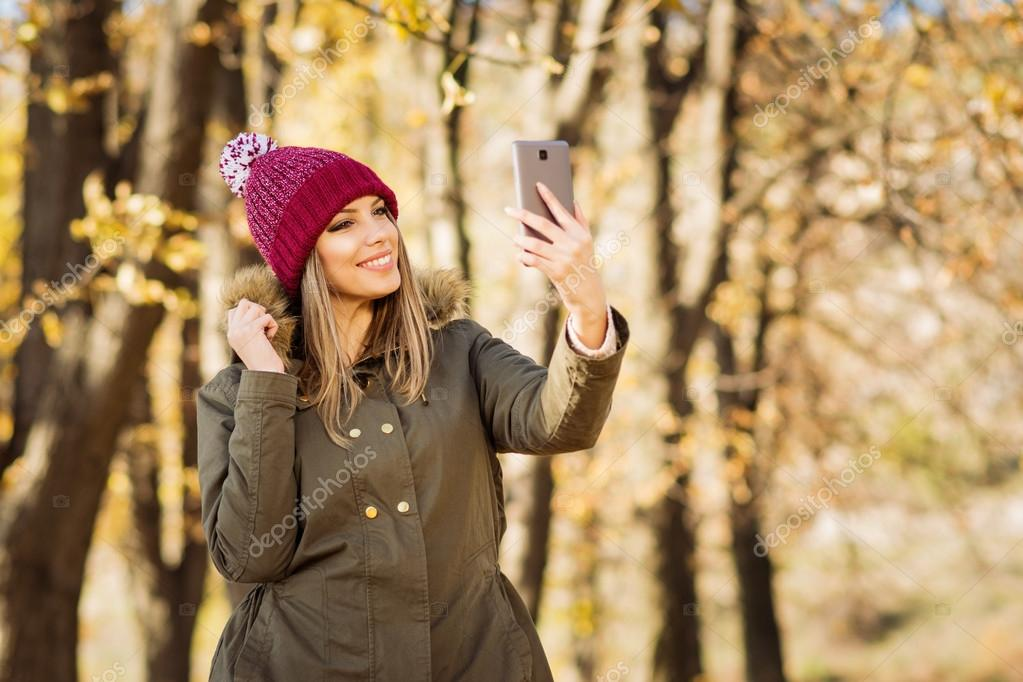 Beautiful young woman in jacket and knitted beanie hat taking a selfie on smart phone in autumn in park