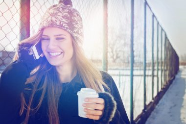 Happy teenage girl with takeaway coffee talking on smartphone