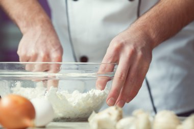 Vegetarian bakery concept. Chef's hands mixing feta cheese and e