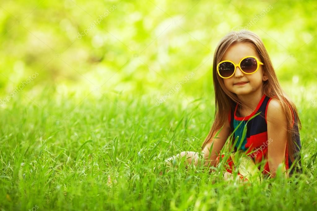 Stylish baby girl with long light brown hair in trendy sunglasses