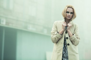 After party concept. Emotive portrait of beautiful blonde in coat