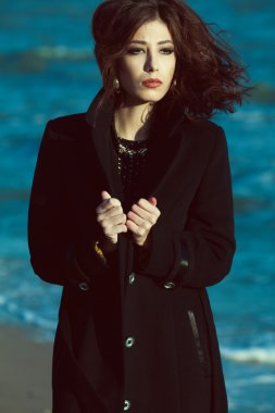 Bella donna concept. Beautiful brunette with long curly hair in coat