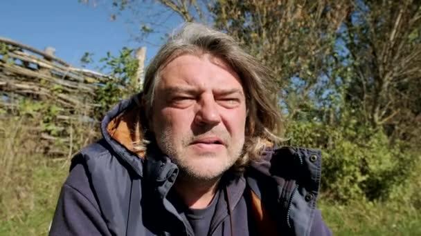 Portrét staršího rybáře kouřícího cigaretu v přírodě. Detailní záběr. Zpomalený pohyb.