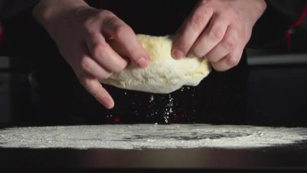 SLOW: Baker throws up a dough on a table in kitchen