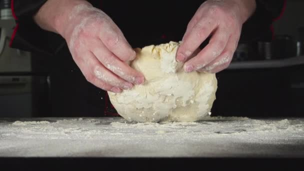 SLOW: A baker kneads a dough in a kitchen