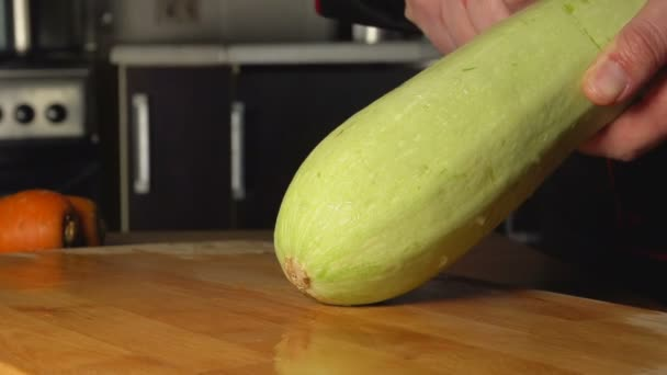 SLOW: Cook cleans a vegetable marrow on a board