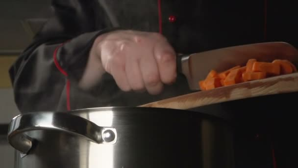 SLOW: Cook throws a sliced carrot into a steel pan