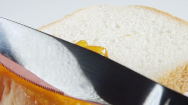 Human hand smears a apricot jam on a bread slice