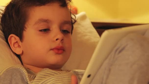 Face of a cute little boy with a white tablet PC at home