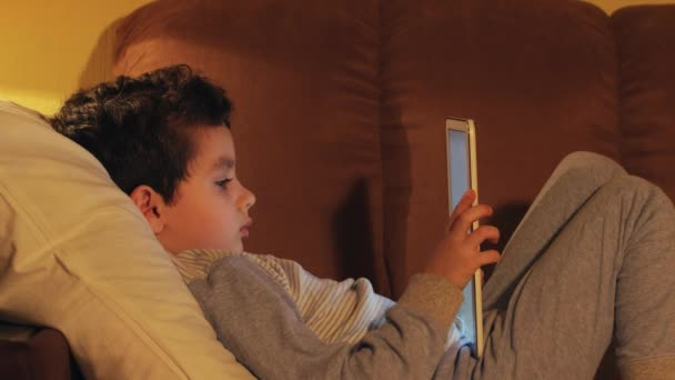 SIDE VIEW: A little boy lays in a bed and looks at a tablet PC at home