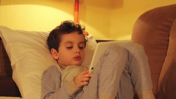 Malý chlapec leží v posteli a dívá na tablet Pc doma