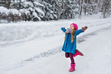 Little girl dressed in a blue coat and a pink hat and boots, running with outstretched arms to the side in the winter forest