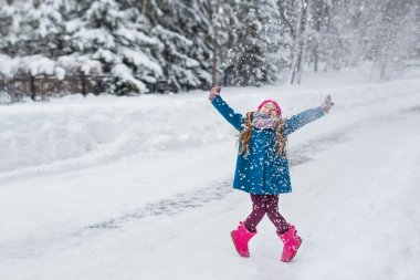 Little girl dressed in a blue coat and a pink hat and boots, hamming and playing in the winter forest