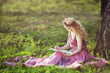 Girl in a fairy dress sitting under a tree in the woods and draws