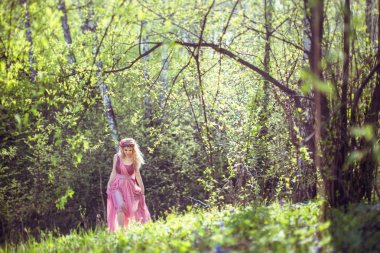 Girl in fairy dress walks in the woods