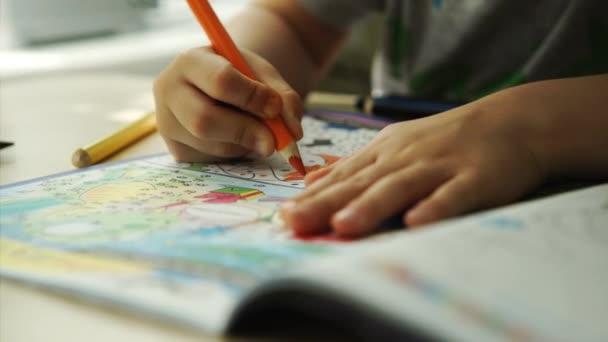 Dětské ruce barvy oranžové tužky na papíře