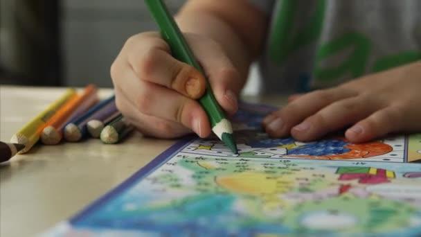 Rukou dítě nakreslí zelené tužky na papíře