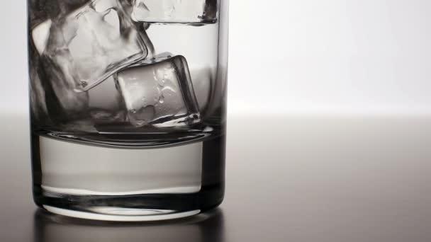 Záběr: Čistá voda kape do sklenice s ledem