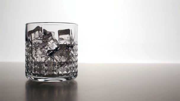 Whiskey önti egy pohárba jeget (balra)