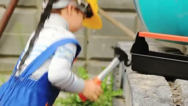 Roztomilý chlapec jako pracovník odpovídají traktoru a sedne si v něm