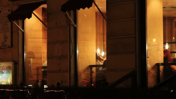 Windows of a restaurant and people are dinning inside