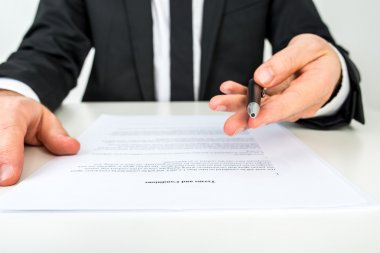 Businessman offering you to sign a document with focus to the te