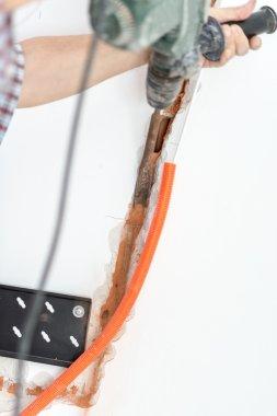 Repairman Installing Orange Corrugated Conduit