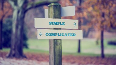 Rustic wooden sign in an autumn park with the words Simple - Com