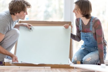 Young couple putting together self assembly furniture