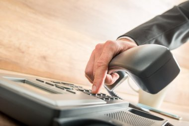 Consultant holding the receiver of a desk phone while dialing