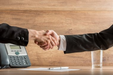 Handshake of business  partners above a written agreement