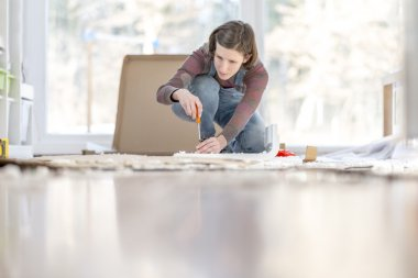 Young Woman assembling a DIY furniture at home kneeling on the f