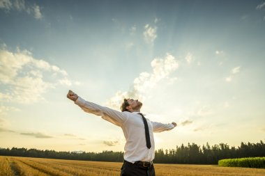 Half Body Shot of a Thankful Young Businessman Looking up the Sky with Wide Open Arms, Standing at the Open Field. stock vector