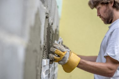 Builder tiling a concrete wall