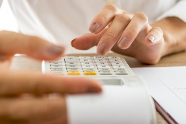 Female banker calculating expenses and income using adding machi