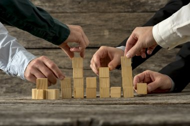 Hands of five businessman holding wooden blocks placing them int