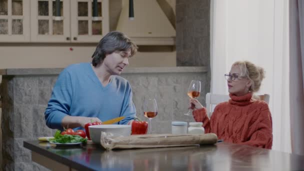 Happy active family couple preparing food and laugh at home. Handsome man and blonde woman have dinner with wine