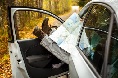 Men's feet with a map in the car. A man travels . Autumn