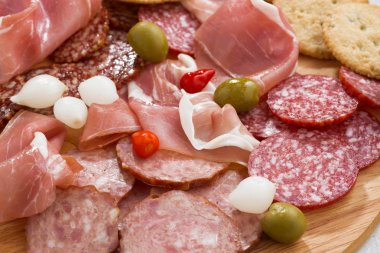 Assorted deli meat snacks, sausages and pickles on board, close-