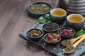 Fotografie assortment of fragrant dried teas and green tea on dark wooden t