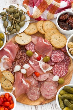 Assorted deli meat snacks, sausages and pickles on board