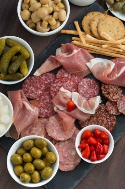 Assorted deli meat snacks, sausages and pickles on a blackboard
