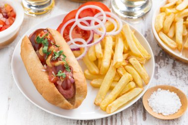 fast food - hot dog with French fries and chips on wooden table