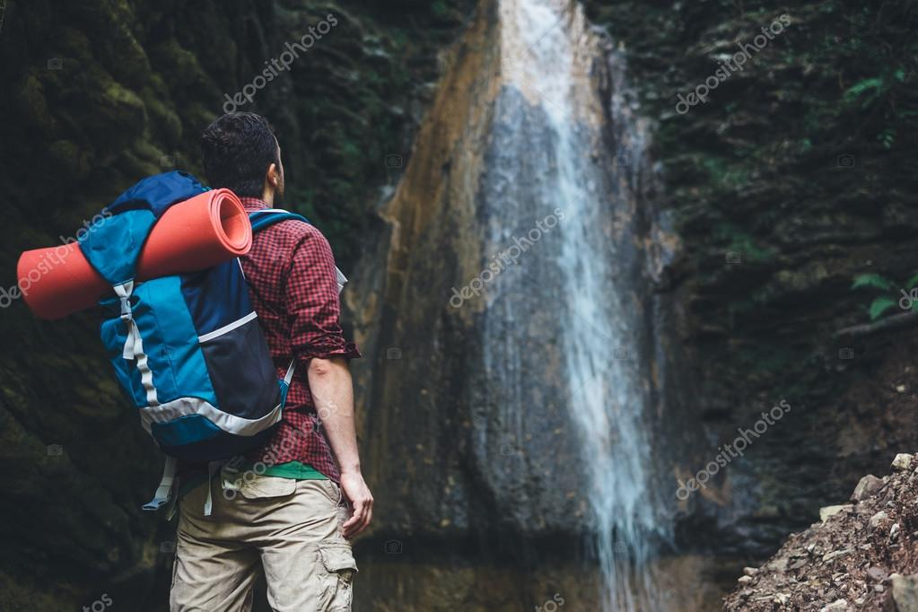 Man next to a waterfall after mountain trekking