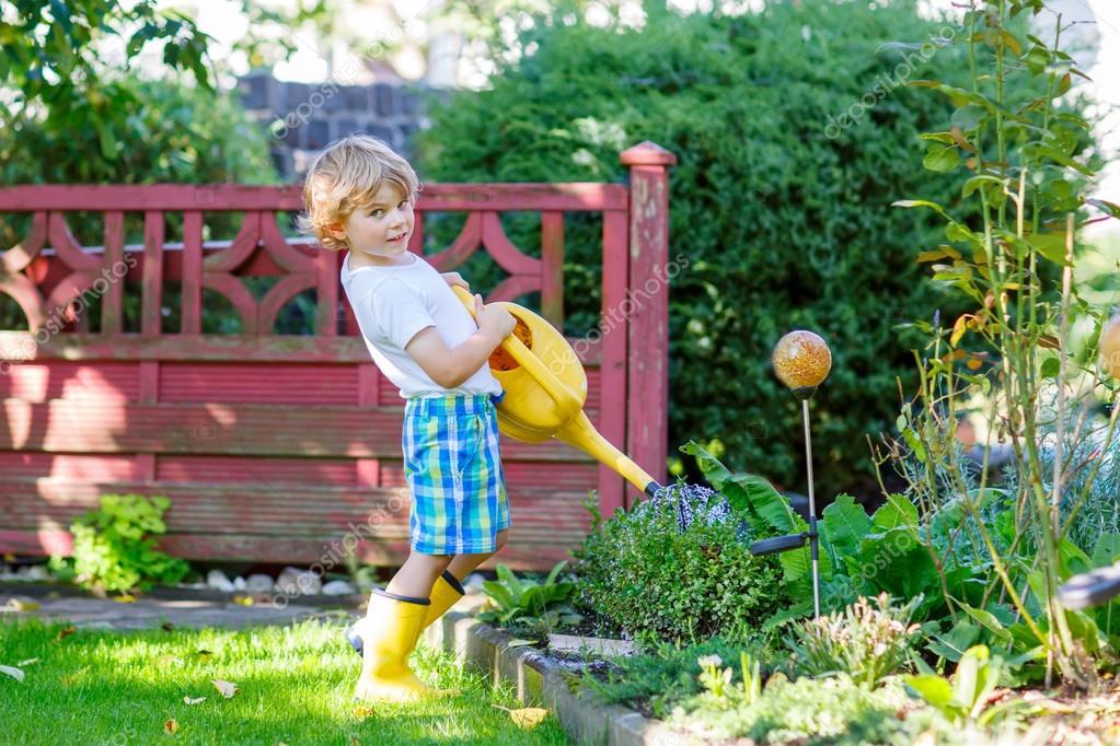 Ni o ni o regar las plantas en el jard n en verano foto for Plantas y jardines fotos