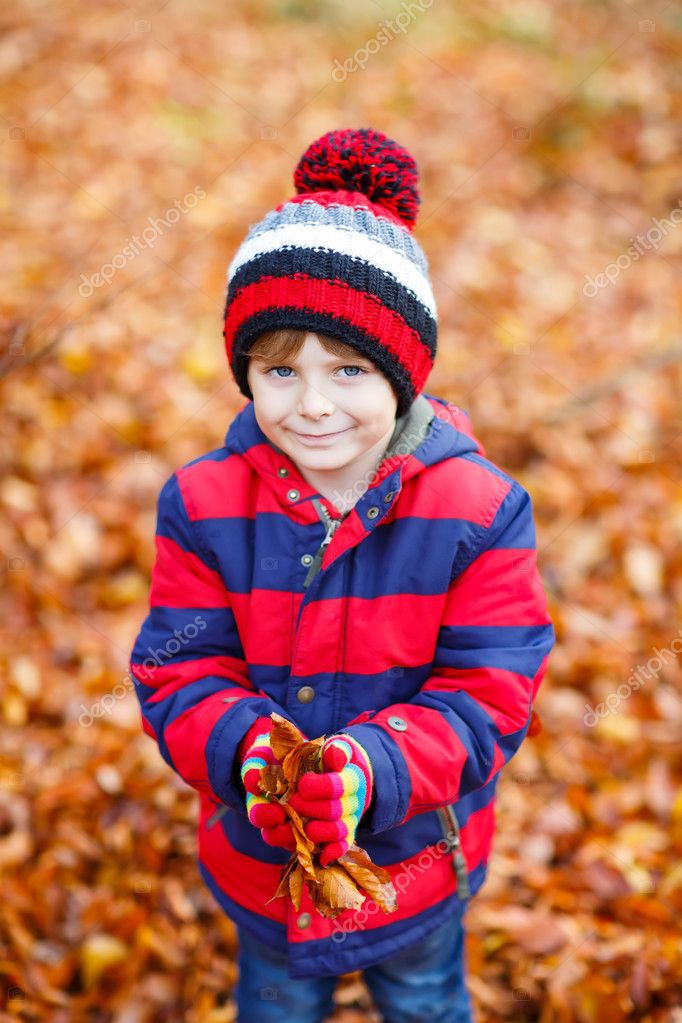 d6639dd7ee3 Funny child having fun in fall forest or park on cold day. With hat and  foliage — Photo ...