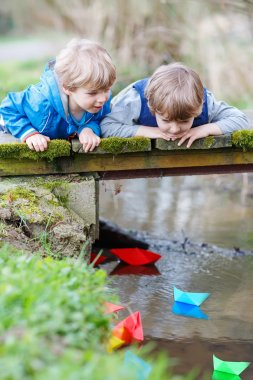 Two little brothers playing with paper boats by a river